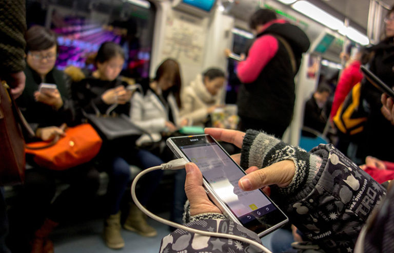 chinese look at cell phone on subway